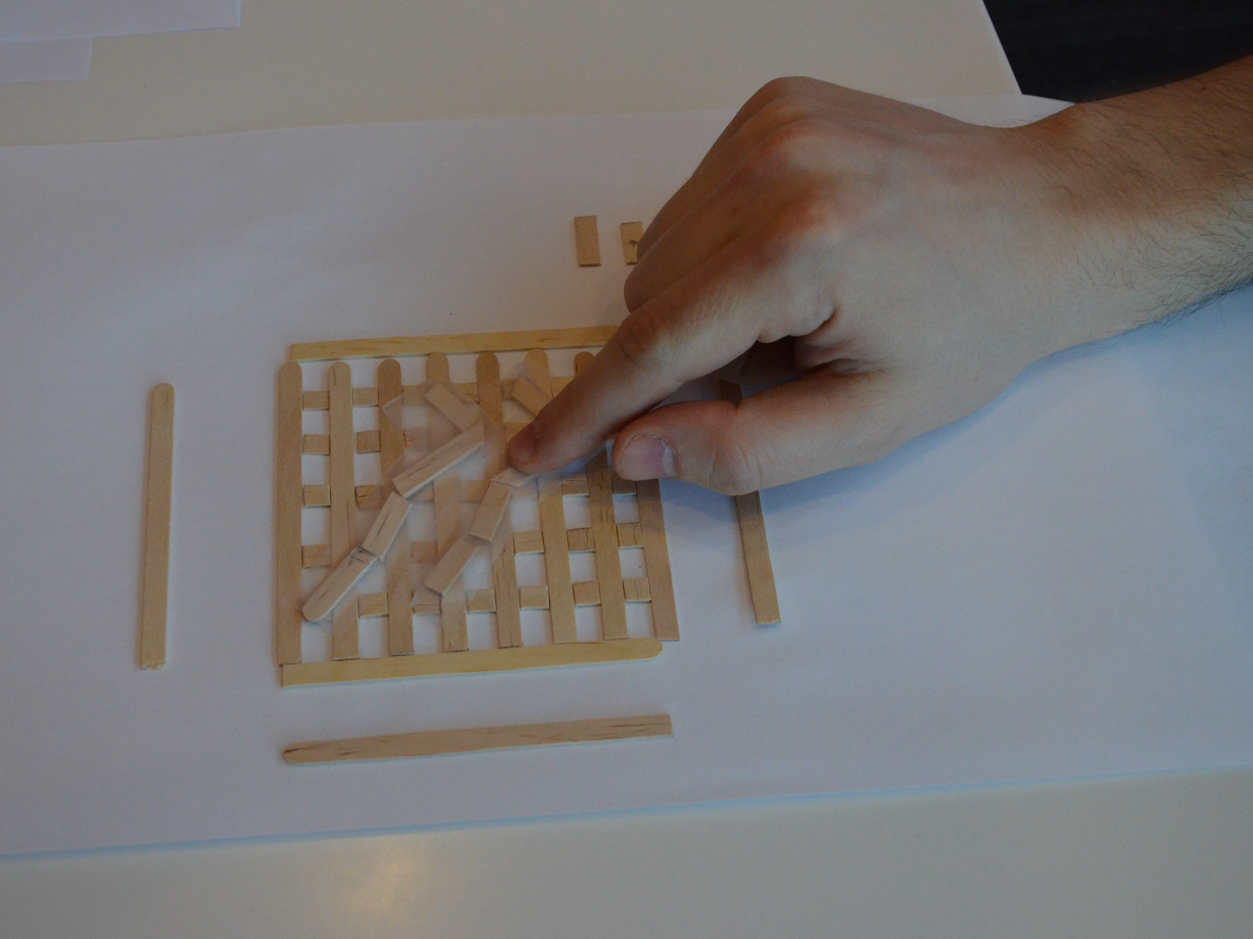 A person feels a rudimentary graph made out of popsicle sticks.