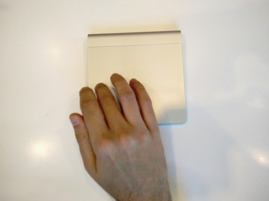 A person drags their finger across a trackpad.